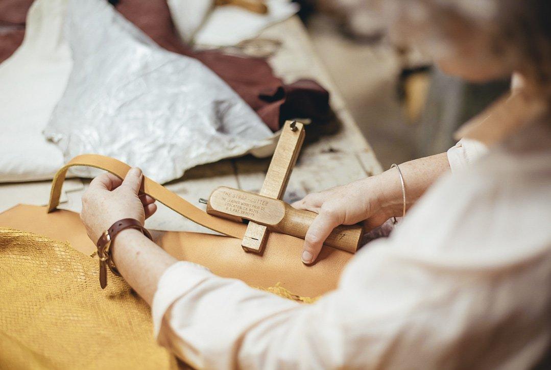 Fotografía profesional de una artesana creando un bolso de cuero